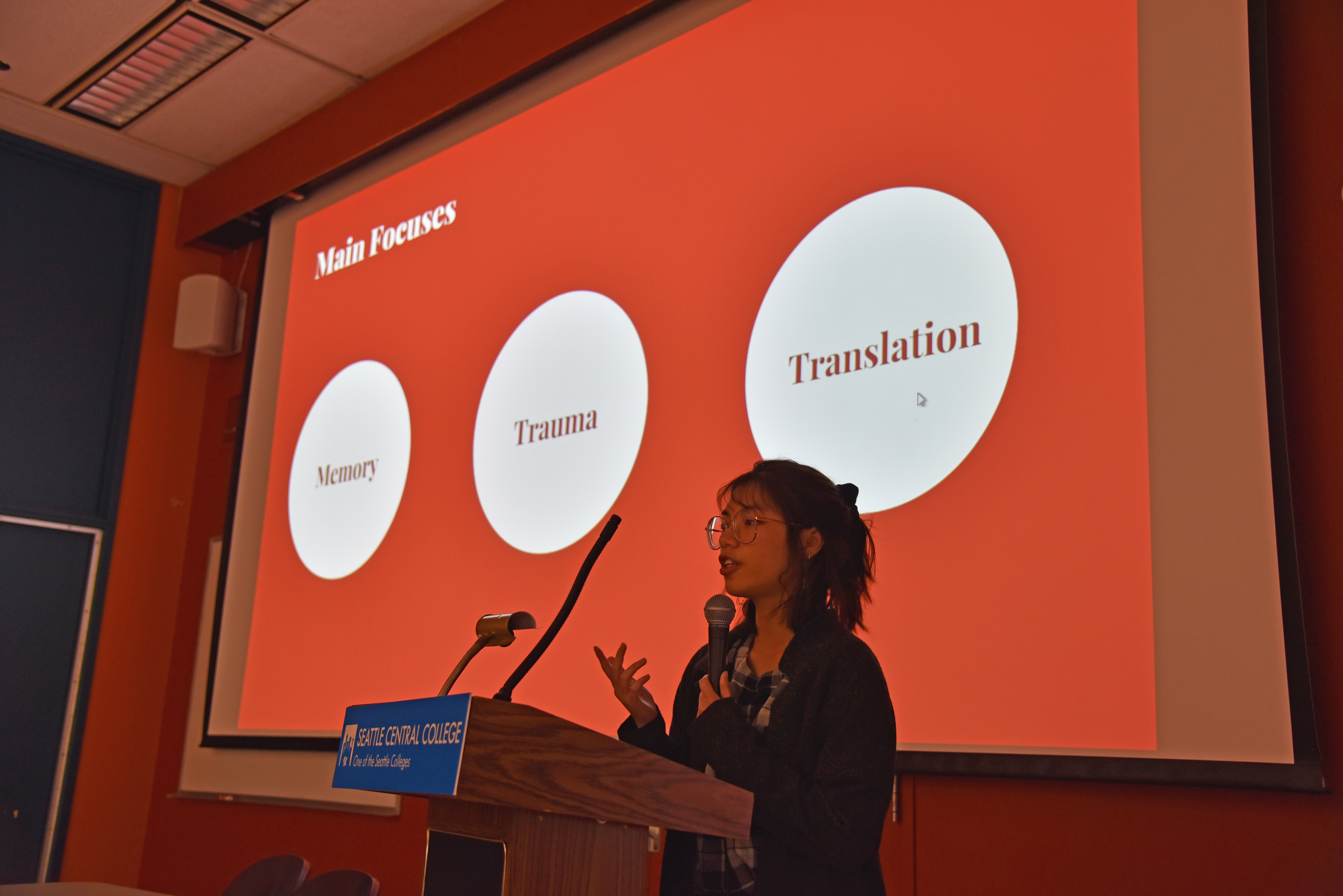 A presenter discusses her proposed CHID project. The screen behind her is in red, with three bubbles featuring the words memory, trauma, translation