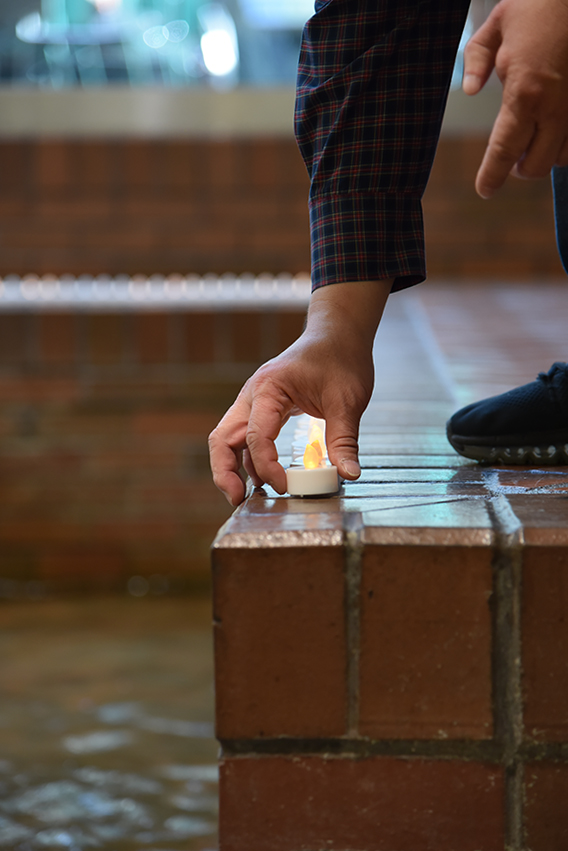 hand places the last memorial candle on the edge of the Atrium fountain
