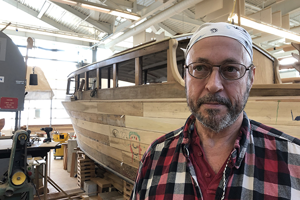 Chef Luke Rinaman poses in front of a practice boat at the Wood Technology Center